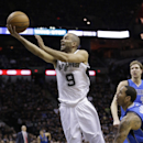 San Antonio Spurs' Tony Parker (9), of France, scores past Dallas Mavericks' Devin Harris, right, during the first quarter of Game 1 of the opening-round NBA basketball playoff series, Sunday, April 20, 2014, in San Antonio The Associated Press