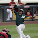Oakland Athletics' Yoenis Cespedes, right, slides into home to score off a single hit by teammate Josh Donaldson as Arizona Diamondbacks catcher Miguel Montero, left, awaits the throw during the first inning of an exhibition spring training baseball game