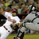 Arizona Diamondbacks' Wil Nieves, right, is tagged out at the plate by San Diego Padres' Nick Hundley during the seventh inning of a baseball game, Friday, May 24, 2013, in Phoenix. (AP Photo/Matt York)