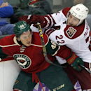 Minnesota Wild's Jared Spurgeon, left, keeps Arizona Coyotes' Brandon McMillan away from a chase for the puck during the third of an NHL hockey game, Thursday, Oct. 23, 2014, in St. Paul, Minn. The Wild won 2-0 The Associated Press