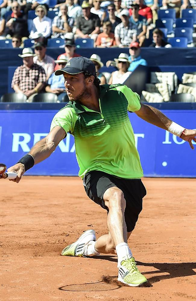 Juan Monaco of Argentina returns a ball to Thomaz Bellucci of Brazil during the quarterfinal match at the Suisse Open tennis tournament in Gstaad, Switzerland, Friday, July 25, 2014