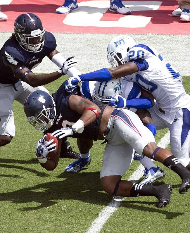 Florida Altantic's Sammy Seamster (8) is stopped by Middle Tennessee's Christian Milstead (18) and Marcus Clark (20) during the first half of an NCAA football game, Saturday, Sept. 21, 2013, in Boca Raton, Fla
