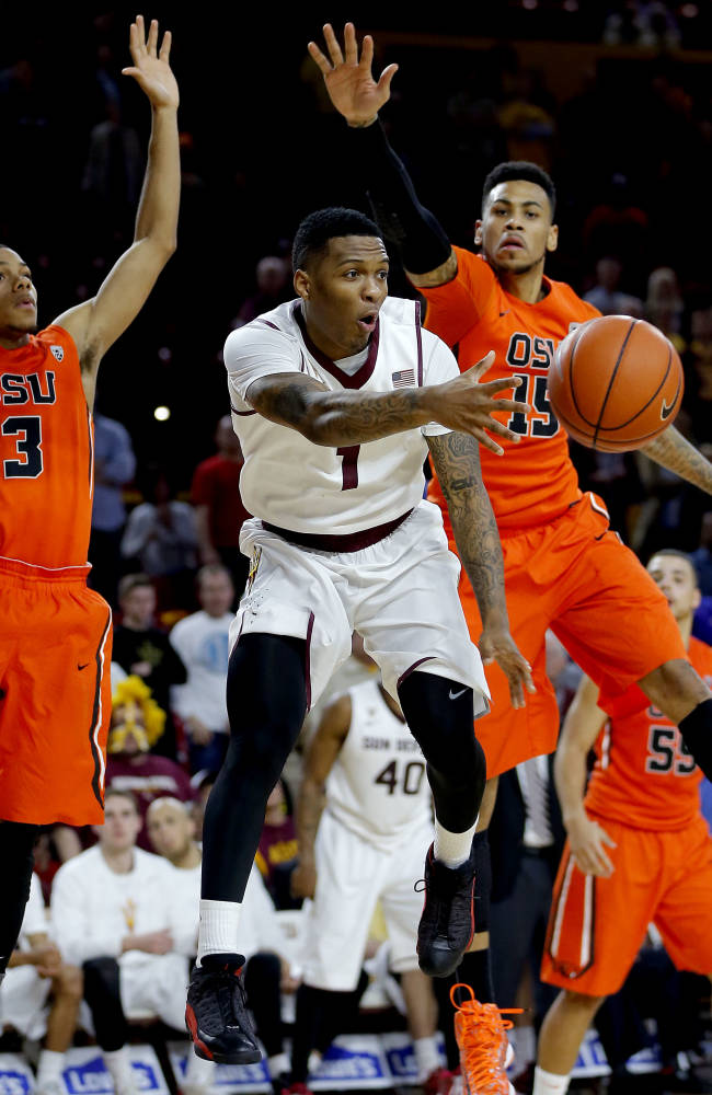 Arizona State's Jahii Carson (1) dishes off as Oregon State's Hallice Cooke (3) and Eric Moreland (15) defend during the second half of an NCAA college basketball game, Thursday, Feb. 6, 2014, in Tempe, Ariz