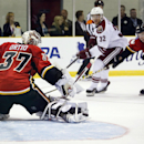 Arizona Coyotes forward Tyler Gaudet, center, looks on as Calgary Flames goalie Joni Ortio kicks his shot away during the second period of an NHL preseason hockey game in Sylvan Lake, Alberta, Wednesday, Sept. 24, 2014. The Associated Press