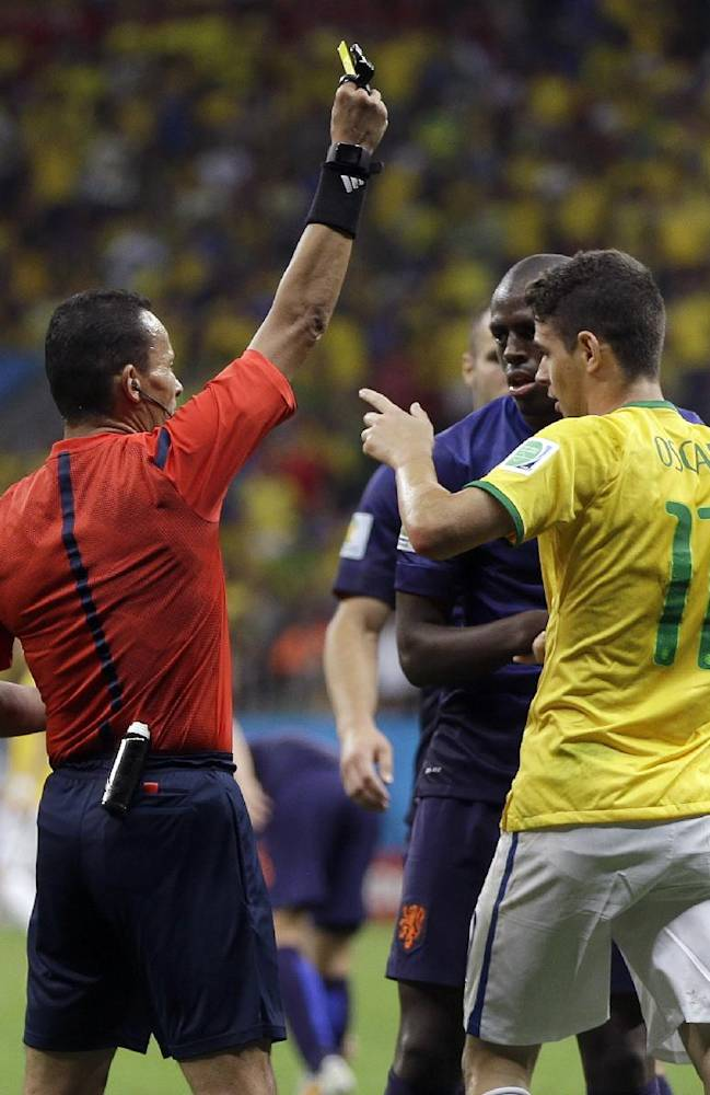 Brazil's Oscar, right, is given a yellow card for diving by referee Djamel Haimoudi, from Algeria, after colliding with Netherlands' Daley Blind during the World Cup third-place soccer match between Brazil and the Netherlands at the Estadio Nacional in Brasilia, Brazil, Saturday, July 12, 2014