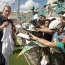 Miami Dolphins quarterback Ryan Tannehill signs autographs for fans after football training camp Friday, July 25, 2014, in Davie, Fla. (AP Photo)