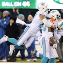 Miami Dolphins strong safety Reshad Jones (20) is mobbed by strong safety Jimmy Wilson (27) and free safety Louis Delmas (25) after intercepting a pass by the New York Jets with seconds left in the fourth quarter of an NFL football game, Monday, Dec. 1, 2