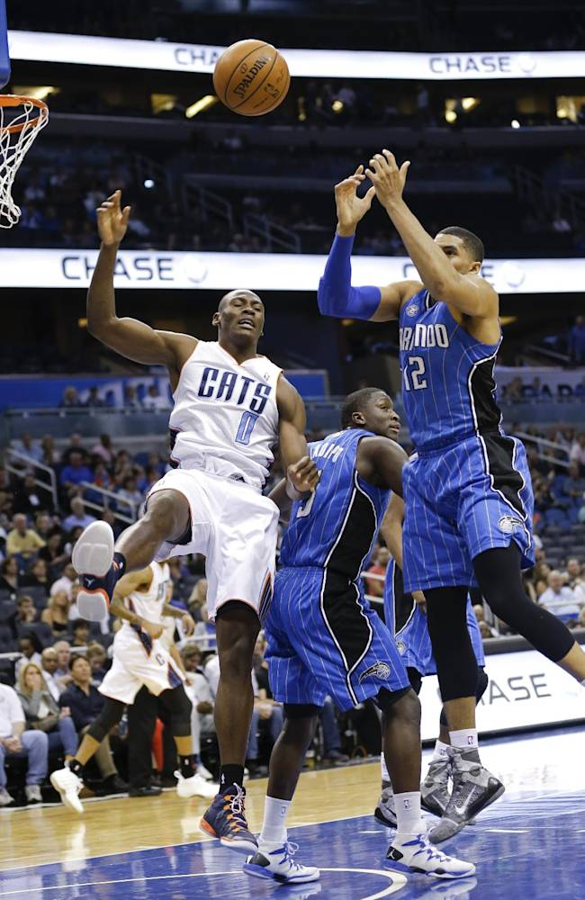 Charlotte Bobcats' Bismack Biyombo (0) and Orlando Magic's Tobias Harris (12) go after a rebound during the first half of an NBA basketball game in Orlando, Fla., Friday, March 28, 2014