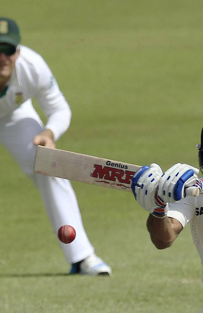 India's batsman Virat Kohli, right, plays a shot as South Africa's captain Graeme Smith, left, watches during second day of their cricket test match at Kingsmead stadium, Durban, South Africa, Friday, Dec. 27, 2013