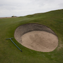 A rake lays next to a bunker on the 13th hole at Royal Liverpool Golf Club before the British Open golf championships, Hoylake, England, Wednesday, April 23, 2014. The 2014 Open Championship which will be played at Royal Liverpool from July 17-20, 2014