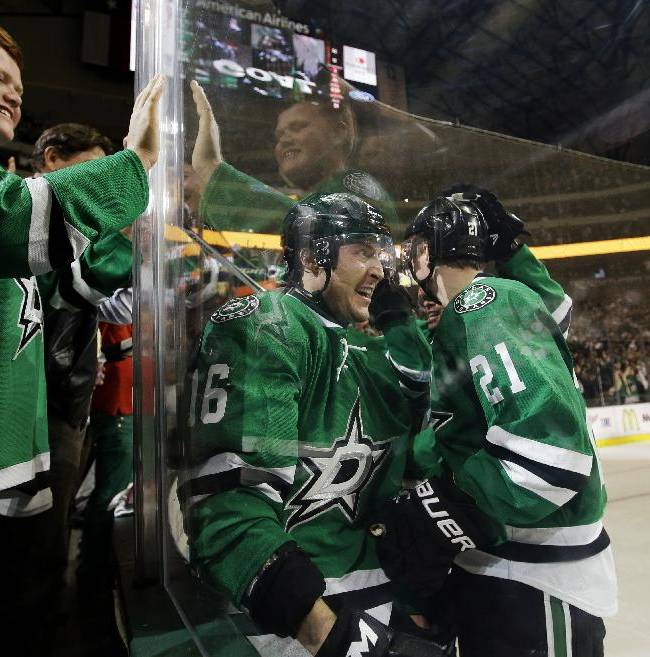 Danny DePinto, left, slaps the glass as he watches Dallas Stars' Ryan Garbutt (16) and Antoine Roussel (21) of France celebrate a goal by Garbutt against the Anaheim Ducks in the third period of Game 3 of a first-round NHL hockey Stanley Cup playoff series game, Monday, April 21, 2014, in Dallas. The Stars won 3-0