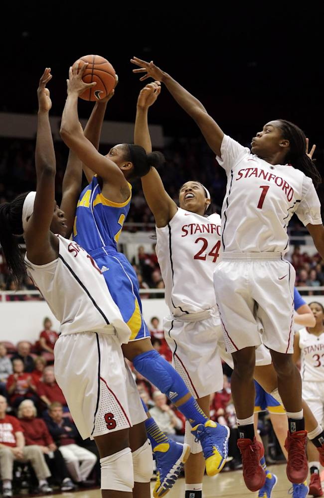 UCLA guard Nirra Fields, in blue, drives to the basket surrounded by Stanford defenders during the second half of an NCAA college basketball game on Friday, Jan. 24, 2014, in Stanford, Calif