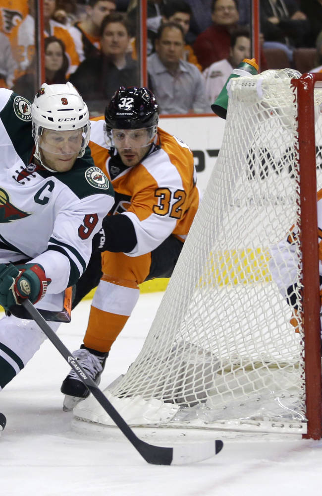 Minnesota Wild's Mikko Koivu (9), of Finland, tries to get a goal past Philadelphia Flyers' Mark Streit (32), of Switzerland, and Flyers' Steve Mason (35) during the first period of an NHL hockey game, Monday, Dec. 23, 2013, in Philadelphia