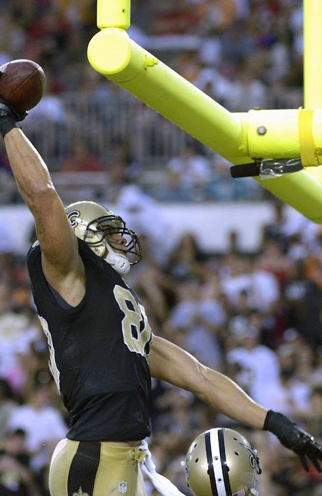 New Orleans Saints tight end Jimmy Graham prepares to dunk the football over the goalpost after scoring on a 56-yard touchdown pass from quarterback Drew Brees during the first quarter of an NFL football game against the Tampa Bay Buccaneers, Sunday, Sept. 15, 2013, in Tampa, Fla