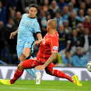 Manchester City's Samir Nasri, left, puts the ball past Liverpool's Martin Skrtel during the English Premier League soccer match between Manchester City and Liverpool at the Etihad Stadium, in Manchester, England, Monday, Aug. 25, 2014