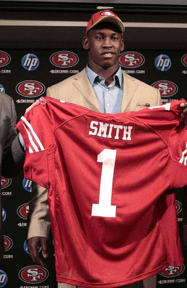 In this April 29, 2011, file photo, Aldon Smith, center, the first-round draft pick of the San Francisco 49ers, holds up a jersey next to coach Jim Harbaugh, left, and general manager Trent Baalke at a news conference at the NFL football team's training facility in Santa Clara, Calif. Baalke is committed to supporting linebacker Smith like a family member in the wake of his latest legal trouble--and keeping Smith around for the long haul, too