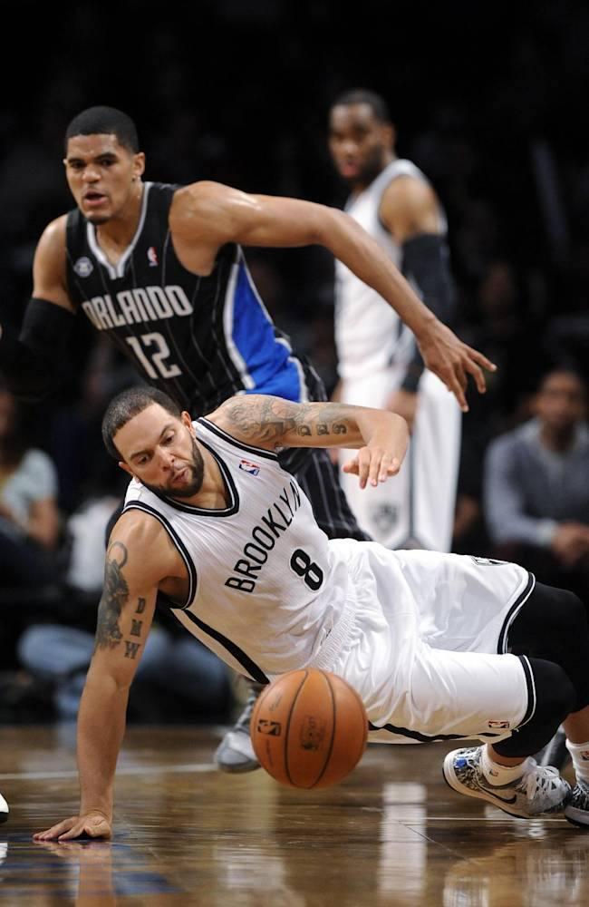 Brooklyn Nets' Deron Williams (8) recovers a loose ball in front of Orlando Magic's Tobias Harris (12) in the second half of an NBA basketball game Sunday, April 13, 2014, in New York. The Nets won 97-88