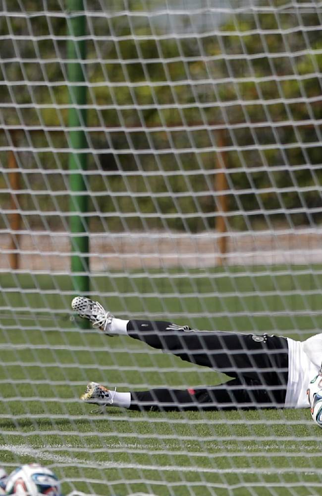German goalkeeper Manuel Neuer, right, catches a ball during a training session near Porto Seguro, Brazil, Monday, June 9, 2014. Germany will play in group G of Brazil's 2014 soccer World Cup