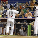 Miami Marlins' Marcell Ozuna (13) is met by teammate Garrett Jones, right, after scoring on a single hit by Giancarlo Stanton during the first inning of an interleague baseball game against the Seattle Mariners, Friday, April 18, 2014, in Miami The Associ