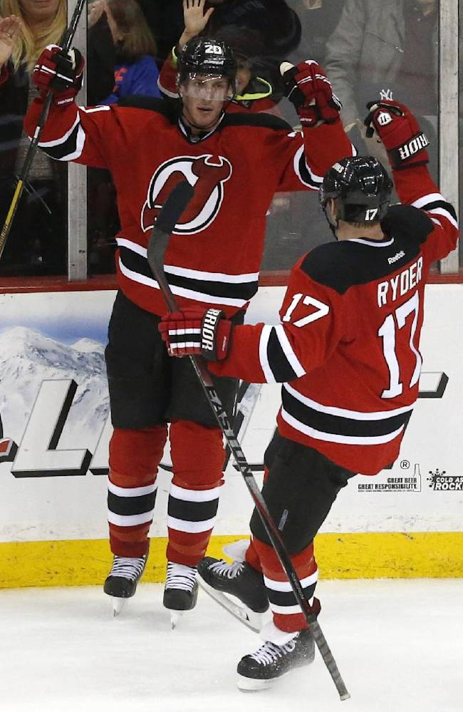 New Jersey Devils' Ryan Carter (20) and Michael Ryder (17) celebrate a goal by Carter against the Washington Capitals during the third period of an NHL hockey game, Friday, April 4, 2014, in Newark, N.J. The Devils won 2-1