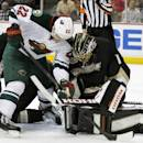 Minnesota Wild right wing Nino Niederreiter (22), of Switzerland battles for the puck with Anaheim Ducks goalie Jonas Hiller, right, of Switzerland with center David Steckel, left, defending in the first period of an NHL hockey game Wednesday, Dec. 11, 2013 in Anaheim, Calif. (AP Photo/Alex Gallardo)