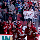 Phoenix Coyotes' Michael Stone, right, and Mike Smith pause along with other players and fans in a moment of silence for the two Phoenix police officers who were shot, one fatally, in a shootout with a suspect in Phoenix on Monday, prior to an NHL hockey