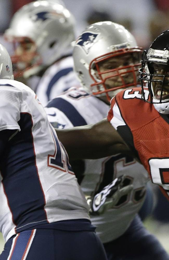 Atlanta Falcons defensive end Malliciah Goodman (93) tries to tackle New England Patriots quarterback Tom Brady (12) during the first half of an NFL football game, Sunday, Sept. 29, 2013, in Atlanta