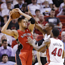 Toronto Raptors center Jonas Valanciunas (17) of Lithuania, looks for an open teammate past Miami Heat forward Udonis Haslem (40) and center Chris Bosh, right rear, during the first half of an NBA basketball game, Monday, March 31, 2014 in Miami The Asso