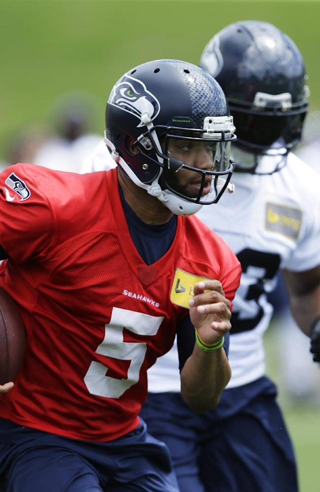 Seattle Seahawks backup quarterback B.J. Daniels keeps the ball during a practice drill at an NFL football organized team activity Monday, June 9, 2014, in Renton, Wash