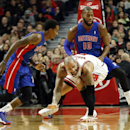 Detroit Pistons guard Brandon Jennings, left, and forward Greg Monroe (10) battle for the loose ball with Chicago Bulls forward Carlos Boozer, center, during the first half of an NBA basketball game in Chicago, Saturday, Dec. 7, 2013 The Associated Press