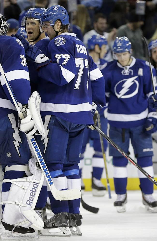 Tampa Bay Lightning goalie Ben Bishop (30) celebrates with teammates, including Victor Hedman (77), of Sweden, after stopping all the Ottawa Senators shots during a shootout in an NHL hockey game Thursday, Jan. 23, 2014, in Tampa, Fla. The Lightning won the game 4-3