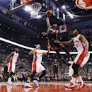 Miami Heat's Dwyane Wade, top, goes to the net against Toronto Raptors' Rudy Gay, right, Jonas Valanciunas, center left, and Amir Johnson, left, during the first half of an NBA basketball game in Toronto, Friday, Nov. 29, 2013 The Associated Press