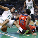 Boston Celtics guard Avery Bradley (0) loses his footing during a scramble for the ball with Washington Wizards forward Nene Hilario (42) during the first quarter of an NBA basketball game in Boston, Wednesday, April 16, 2014 The Associated Press