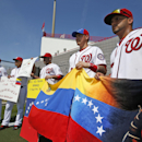 Washington Nationals' Gabriel Alfaro, left, Wilson Ramos, Sandy Leon, Jose Lobaton, and Jhonatan Solano hold flags and signs for reporters after a spring training baseball workout, Sunday, Feb. 23, 2014, in Kissimmiee, Fla. The players are asking for an e