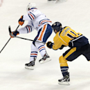 Edmonton Oilers center Jordan Eberle, left, scores an empty-net goal as he is defended by Nashville Predators forward David Legwand (11) in the third period of an NHL hockey game Thursday, Nov. 28, 2013, in Nashville, Tenn. The Oilers won 3-0 The Associat