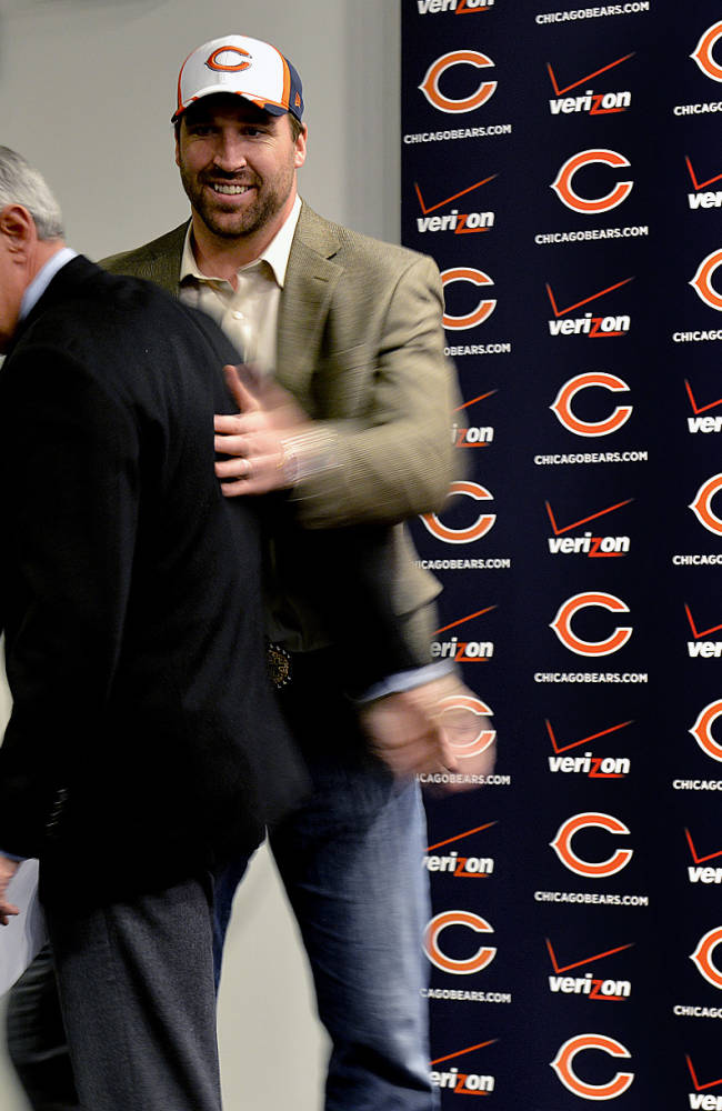 Chicago Bears general manager Phil Emery, center, gets a pat on the back from new Chicago Bears NFL football player Jared Allen, right, during a news conference where Allen was introduced Monday, March 31, 2014, in Lake Forest, Ill