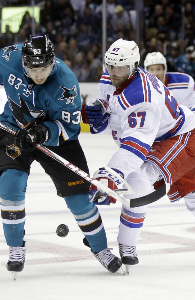 San Jose Sharks' Matt Nieto (83), left, is defended by New York Rangers' Benoit Pouliot (67) during the second period of an NHL hockey game on Tuesday, Oct. 8, 2013, in San Jose, Calif