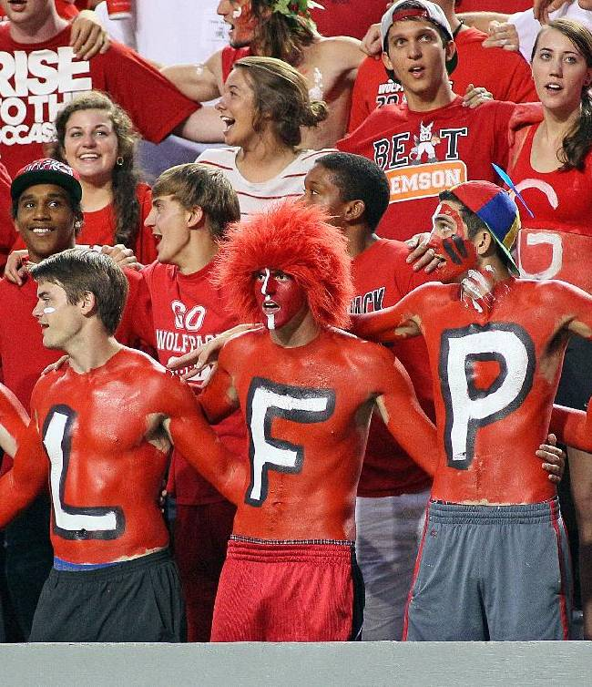 North Carolina State fans don body paint during the first half of an NCAA college football game against Clemson, in Raleigh, N.C., Thursday, Sept. 19, 2013. Clemson won 26-14