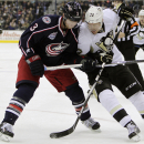 Columbus Blue Jackets' Jordan Leopold, left, and Pittsburgh Penguins' Patric Hornqvist, of Sweden, fight for a loose puck during the first period of an NHL hockey game Saturday, Dec. 13, 2014, in Columbus, Ohio The Associated Press