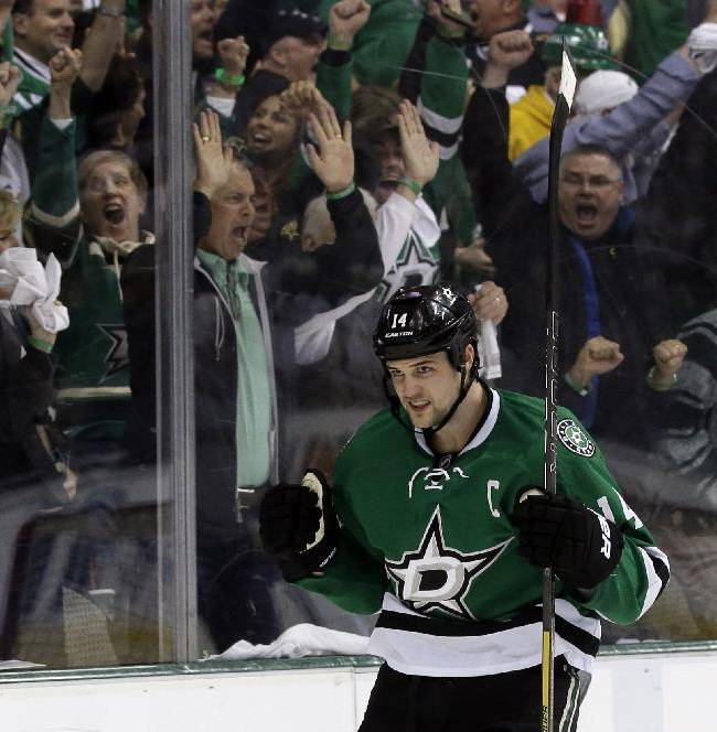 Fans celebrate along with Dallas Stars left wing Jamie Benn (14) after a score by Benn in the first period of Game 3 of a first-round NHL hockey Stanley Cup playoff series game, Monday, April 21, 2014, in Dallas