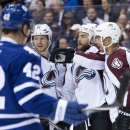 Toronto Maple Leafs' Tyler Bozak watches as Colorado Avalanche center Ryan O'Reilly, center, is congratulated on his goal by teammates Jarome Iginla, right, and Gabriel Landeskog during the first period of an NHL hockey game Tuesday, Oct. 14, 2014, in Tor