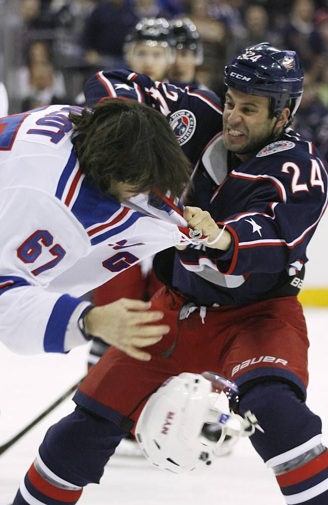 Columbus Blue Jackets' Derek MacKenzie (24) fights New York Rangers' Benoit Pouliot (67) during the first period of an NHL hockey game, Friday, March 21, 2014, in Columbus, Ohio