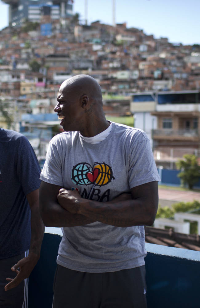 Washington Wizards' Trevor Ariza, left, and Al Harrington joke as they pose for photos during a visit to the Complexo do Alemao slum in Rio de Janeiro, Brazil, Friday, Oct. 11, 2013. Brazilian Nene Hilario led his teammates to the pacified shantytown in the city's north side. They met with dozens of children at a sports complex inside the slum and held a brief clinic with local residents. The Wizards are in Brazil preparing for NBA's first exhibition game in South America against the Chicago Bulls on Saturday