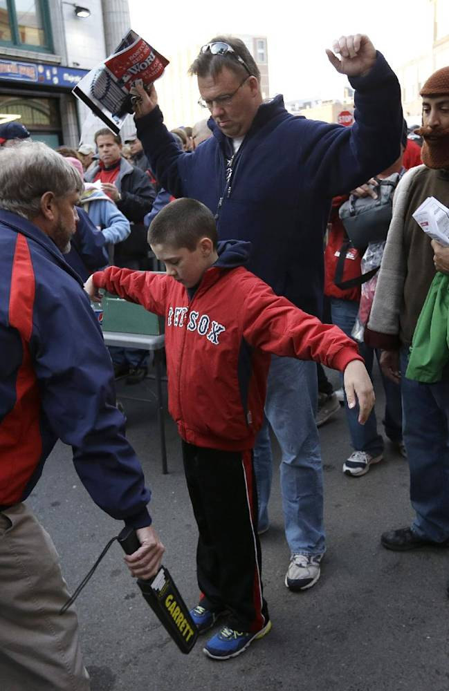In this Oct. 30, 2013 file photo, Jeffrey Corbett, top, and his son Joseph, 9, center, both of Arlington, Mass., raise their arms as they pass through security outside Fenway Park before Game 6 of baseball's World Series between the Boston Red Sox and St. Louis Cardinals, in Boston. Baseball fans should expect to go through a metal detector to see their team play in 2014. MLB security director John Skinner says at a panel discussion at Harvard that the commissioner's office plans to recommend walkthrough metal detectors