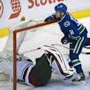 Minnesota Wild goalie Devan Dubnyk (40) falls backwards after being knocked by Vancouver Canucks right wing Derek Dorsett (51) during the third period of NHL action in Vancouver, British Columbia, Canada, Sunday, Feb. 1, 2015 The Associated Press