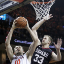 Virginia forward Mike Tobey (10) puts up a layup in front of Harvard forward Evan Cummins (33) during the first half of an NCAA college basketball game in Charlottesville, Va., Sunday, Dec. 21, 2014. (AP Photo/Ryan M. Kelly)