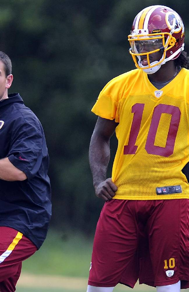In this Aug. 16, 2012, file photo, Washington Redskins quarterback coach Matt LaFleur, left, works with quarterback Robert Griffin III during NFL football training camp in Ashburn, Va. Notre Dame head football coach Brian Kelly announced Friday, Jan. 24, 2014, that they hired LaFleur as the team's new quarterbacks coach