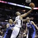San Antonio Spurs' Tony Parker (9), of France, shoots around Dallas Mavericks' Shawn Marion, left, and Dirk Nowitzki (41), of Germany, during the first half of Game 2 of the opening-round NBA basketball playoff series on Wednesday, April 23, 2014, in San