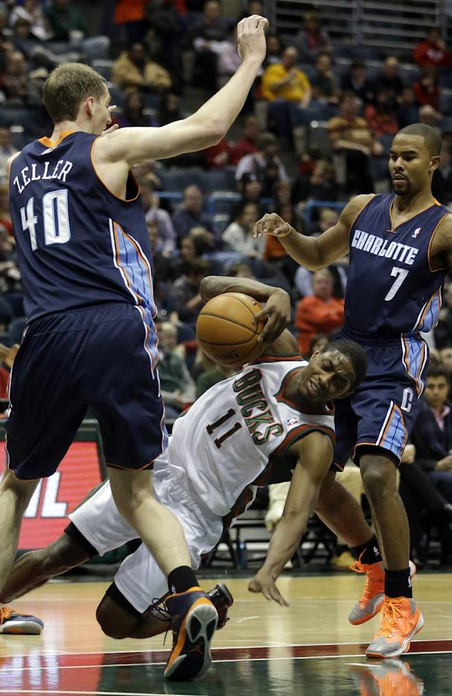 Milwaukee Bucks' Brandon Knight falls as he drives between Charlotte Bobcats' Cody Zeller (40) and Ramon Sessions during the second half of an NBA basketball game on Saturday, Nov. 23, 2013, in Milwaukee