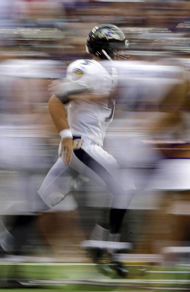 In this picture made with a slow shutter speed, Baltimore Ravens quarterback Joe Flacco, center, runs past teammates and cheerleaders after being introduced before an NFL preseason football game against the San Francisco 49ers, Thursday, Aug. 7, 2014, in Baltimore